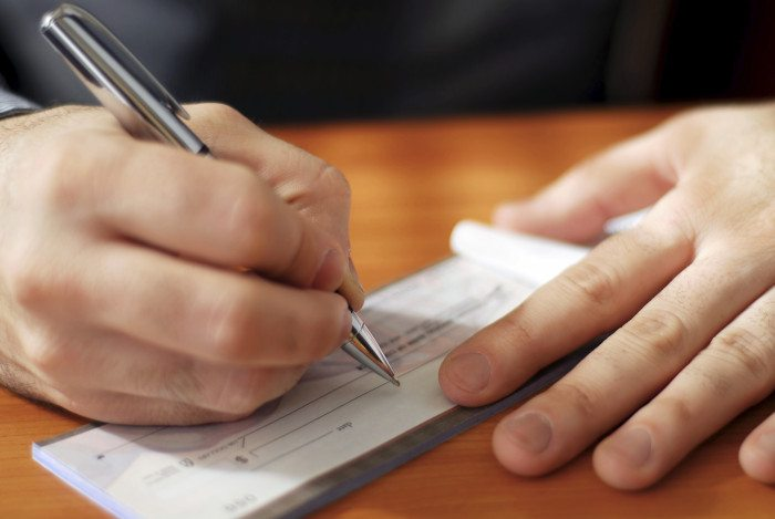 Closeup On Man's Hands Writing A Check In A Checkbook. (Credit: IStock)