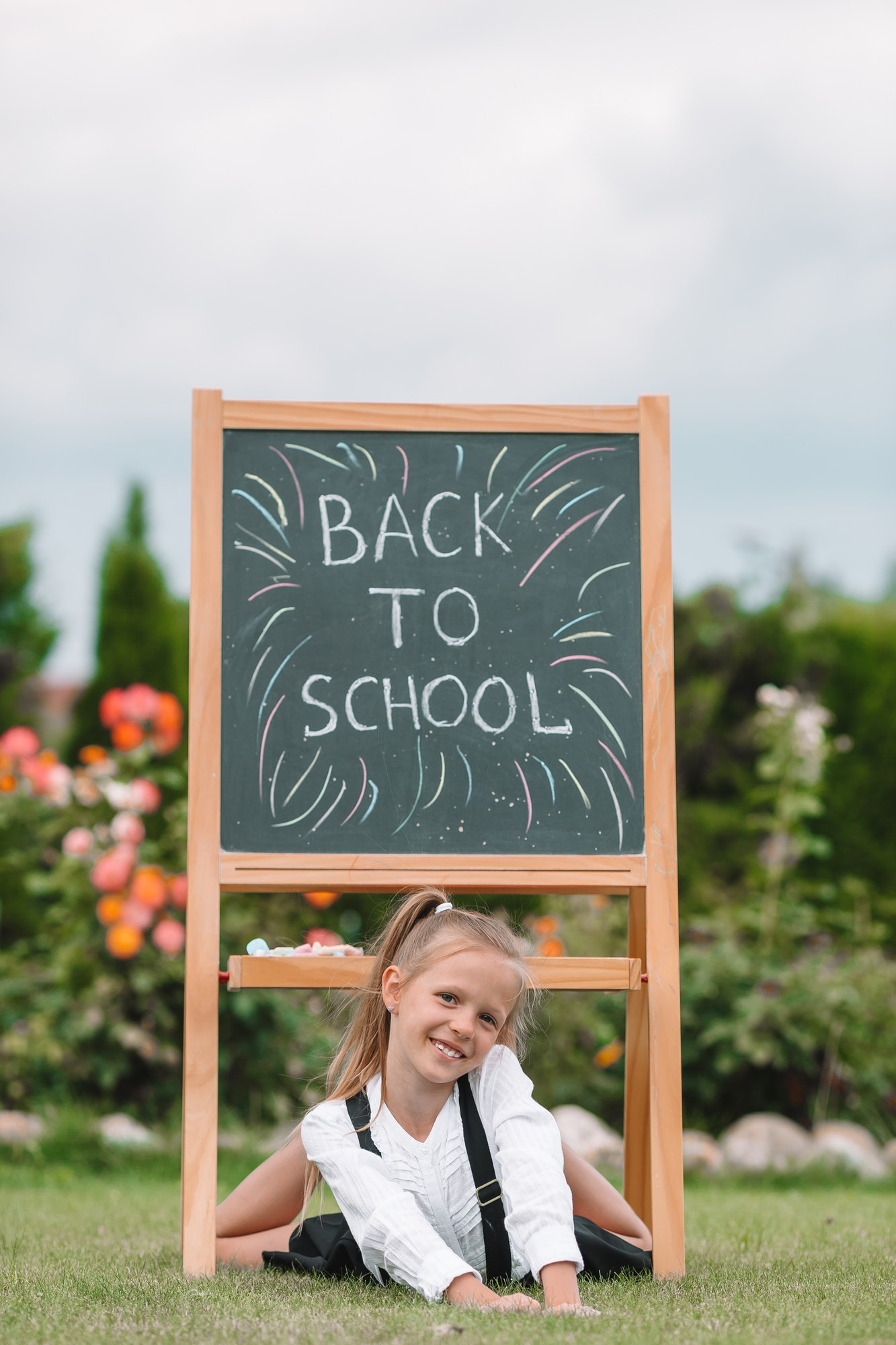 Happy little schoolgirl with a chalkboard outdoor