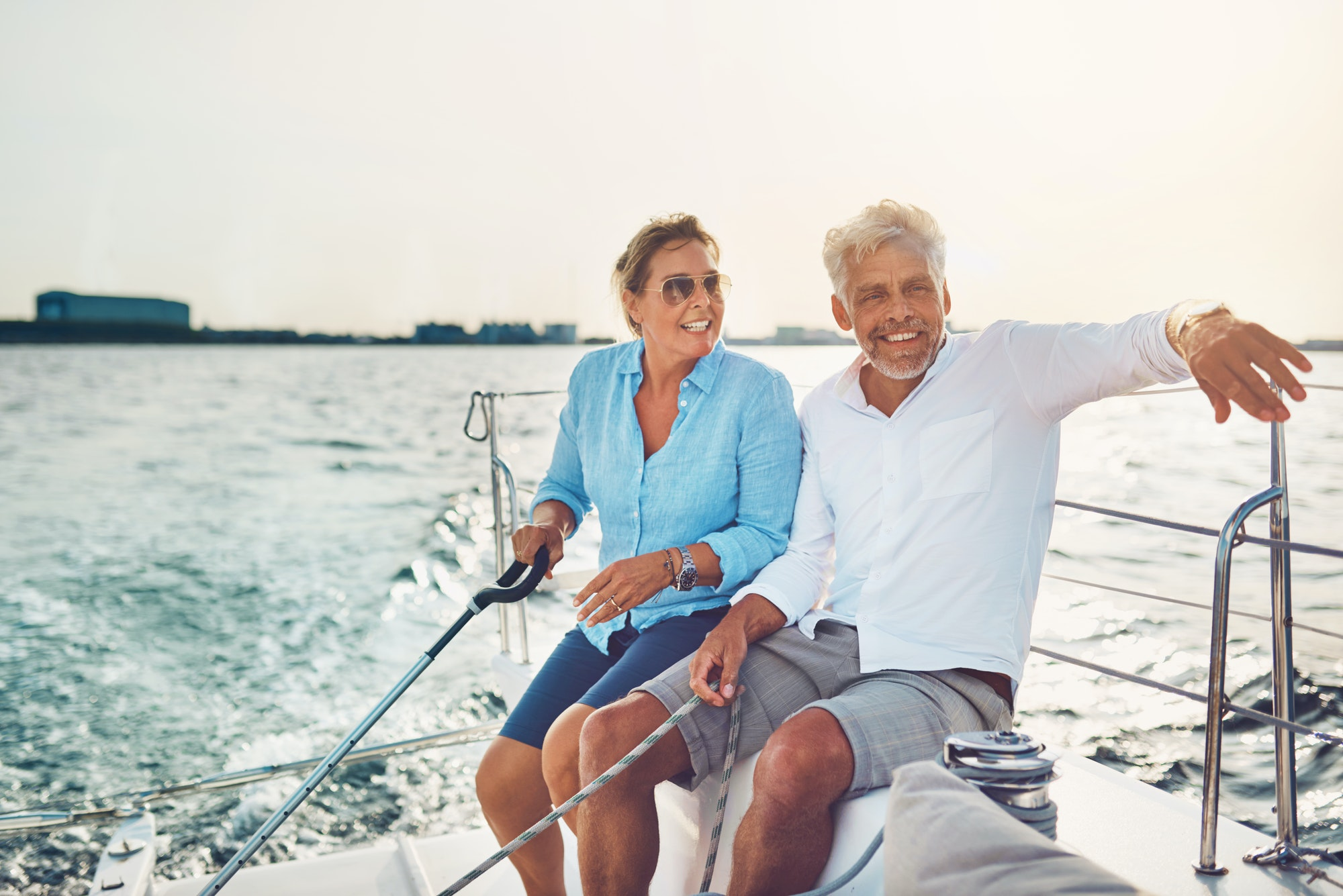 Smiling mature couple sailing their boat on a sunny afternoon